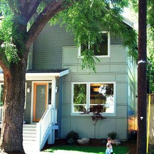 Ejemplo de fachada verde, minimalista, de tamaño medio, de dos plantas, con revestimiento de madera y tejado a dos aguas