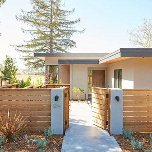 Idéer för ett modernt beige hus, med platt tak