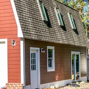 Imagen de fachada de casa roja, de estilo de casa de campo, grande, de una planta, con revestimiento de aglomerado de cemento, tejado a doble faldón y tejado de teja de madera