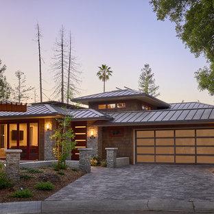 Foto de fachada de casa marrón, rural, grande, de dos plantas, con tejado a cuatro aguas, tejado de metal y revestimientos combinados