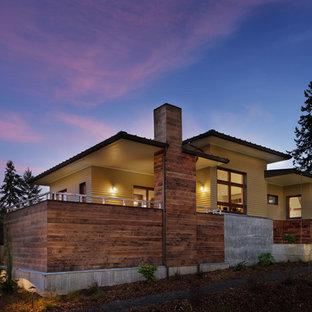 Imagen de fachada de casa amarilla, actual, de tamaño medio, de dos plantas, con revestimientos combinados, tejado de un solo tendido y tejado de metal