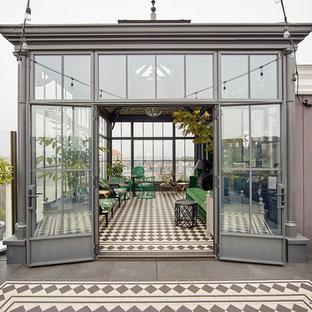 Foto de fachada gris, bohemia, de tres plantas, con revestimiento de vidrio y tejado de metal