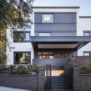Пример оригинального дизайна: трехэтажный, белый дом в современном стиле с плоской крышей