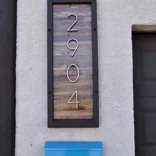Réalisation d'une petit façade de maison marron minimaliste de plain-pied avec un revêtement en stuc et un toit plat.
