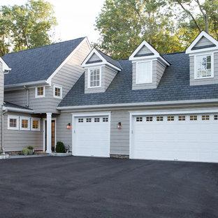 Modelo de fachada gris, tradicional, grande, a niveles, con revestimiento de madera y tejado de un solo tendido