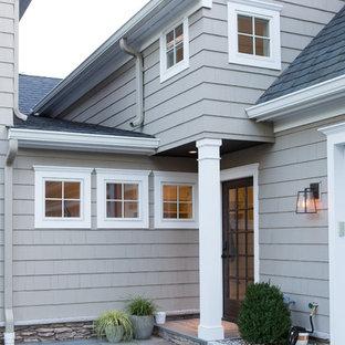 Foto de fachada gris, clásica, grande, a niveles, con revestimiento de madera y tejado de un solo tendido