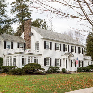 Example of a large classic white exterior home design in New York with a shingle roof
