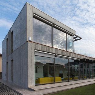 Modelo de fachada gris, urbana, de tamaño medio, de dos plantas, con revestimiento de hormigón y tejado plano