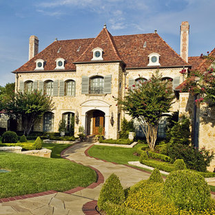 Example of a french country two-story stone exterior home design in Dallas