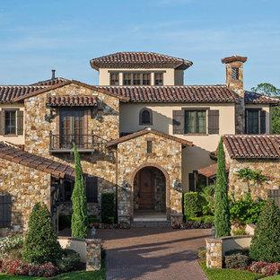 Diseño de fachada de casa beige, mediterránea, extra grande, de tres plantas, con revestimientos combinados, tejado a dos aguas y tejado de teja de barro