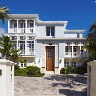 Dreistöckiges, Blaues Tropenstil Haus mit Holzfassade und Flachdach in Miami