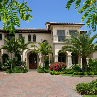 Inspiration for a large mediterranean two-storey stucco beige exterior in Miami with a hip roof.