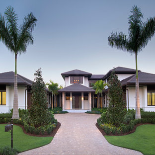 Island style white two-story stucco exterior home photo in Miami with a hip roof and a tile roof