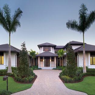 Réalisation d'une façade de maison blanche ethnique à un étage avec un revêtement en stuc, un toit à quatre pans et un toit en tuile.