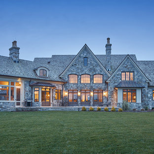 Example of a classic gray stone exterior home design in Baltimore with a shingle roof