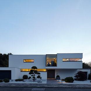 Modern inredning av ett mellanstort vitt hus, med två våningar, stuckatur och platt tak
