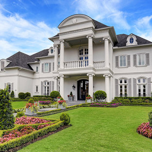 Elegant white two-story house exterior photo in Houston with a hip roof and a shingle roof