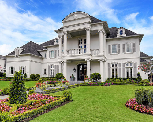 elegant white two story exterior home photo in houston with a hip roof and a