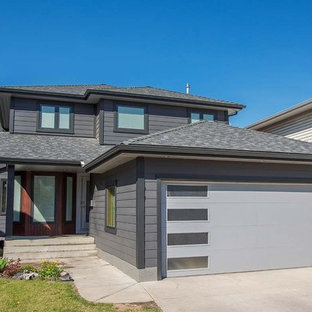 Inspiration for a mid-sized modern gray two-story vinyl house exterior remodel in Calgary with a hip roof and a shingle roof