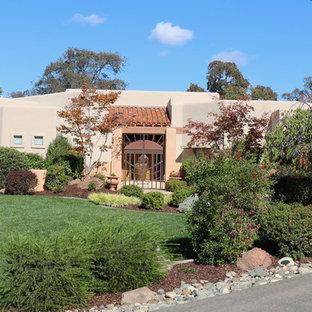 Large southwestern beige one-story stucco flat roof idea in Sacramento