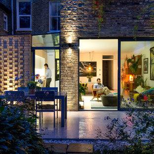 Foto de fachada de casa pareada amarilla, minimalista, pequeña, de una planta, con revestimiento de ladrillo, tejado plano y tejado de varios materiales