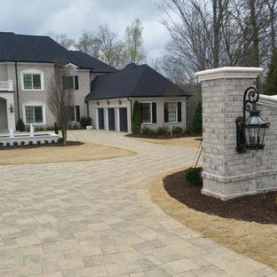 Large elegant gray two-story stone exterior home photo in Atlanta with a hip roof