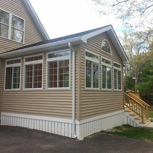 Imagen de fachada beige, clásica, de tamaño medio, de dos plantas, con revestimiento de vinilo y tejado a doble faldón