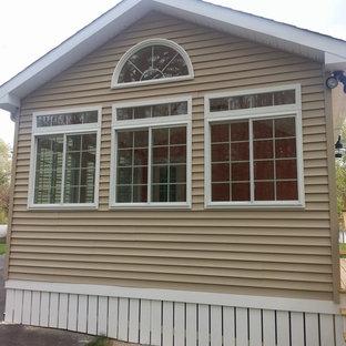 Diseño de fachada beige, clásica, de tamaño medio, de dos plantas, con revestimiento de vinilo y tejado a doble faldón