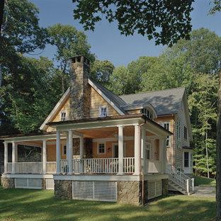 Modelo de fachada de casa amarilla, romántica, grande, a niveles, con revestimiento de piedra y tejado a la holandesa