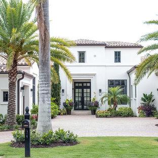 Foto de fachada de casa blanca, mediterránea, de dos plantas, con tejado de teja de barro