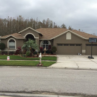 Large trendy brown split-level stucco exterior home photo in Tampa