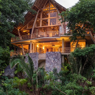 Inspiration for a tropical beige two-story glass exterior home remodel in Hawaii