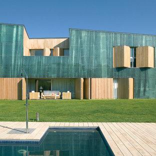 Imagen de fachada verde, contemporánea, extra grande, de dos plantas, con revestimientos combinados y tejado de un solo tendido