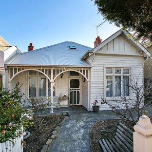 Foto della facciata di una casa bianca shabby-chic style a due piani con rivestimento in legno