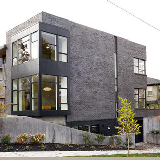 Small modern black three-story brick exterior home idea in Seattle with a mixed material roof