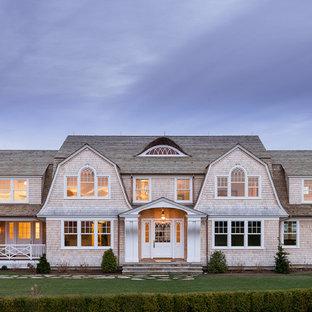 Foto de fachada de casa beige, costera, extra grande, de dos plantas, con revestimiento de madera, tejado a doble faldón y tejado de teja de madera