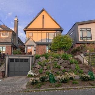 Imagen de fachada de casa multicolor, actual, grande, de tres plantas, con revestimiento de ladrillo, tejado a dos aguas y tejado de teja de madera