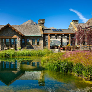 Mountain style two-story stone exterior home photo in Other