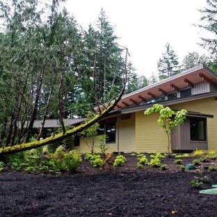 Example of a mid-sized trendy yellow one-story wood house exterior design in Seattle with a gambrel roof and a metal roof