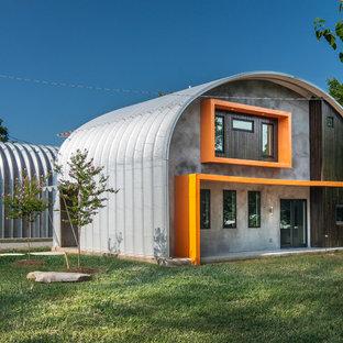 Exemple d'une façade de maison orange industrielle de taille moyenne et à un étage avec un toit en métal.