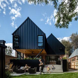 На фото: черный частный загородный дом в стиле кантри с двускатной крышей с