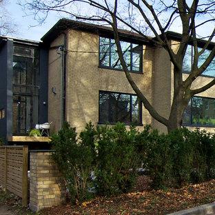 Ejemplo de fachada amarilla, minimalista, de dos plantas, con revestimiento de ladrillo y tejado a cuatro aguas