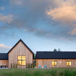 Пример оригинального дизайна: большой, одноэтажный, деревянный, коричневый частный загородный дом в скандинавском стиле с двускатной крышей и крышей из гибкой черепицы
