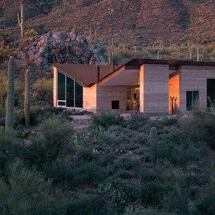 На фото: частный загородный дом в стиле модернизм с облицовкой из самана, крышей-бабочкой и металлической крышей