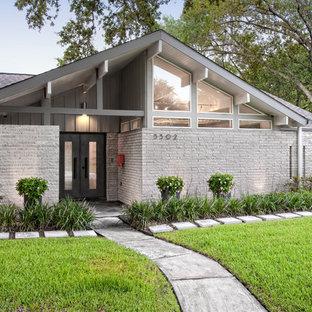 Diseño de fachada de casa gris, vintage, de tamaño medio, de una planta, con revestimiento de ladrillo, tejado a dos aguas y tejado de teja de madera