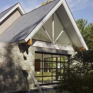 Ispirazione per la facciata di una casa piccola grigia contemporanea a un piano con rivestimento in pietra e tetto a capanna