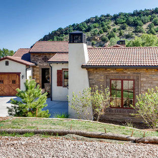 Tuscan one-story stone house exterior photo in Denver with a hip roof and a tile roof