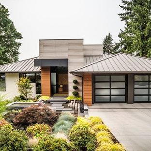 Foto på ett mellanstort 50 tals flerfärgat hus, med blandad fasad, valmat tak och tak i metall