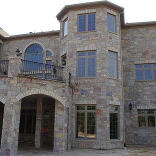 Ejemplo de fachada de casa multicolor, bohemia, extra grande, de tres plantas, con revestimiento de piedra y tejado de teja de madera