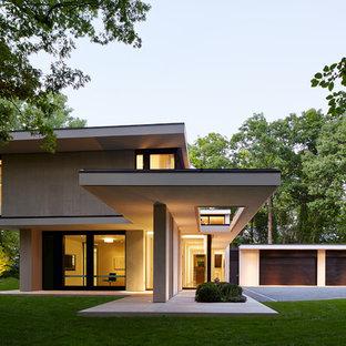 На фото: двухэтажный, бежевый частный загородный дом в стиле модернизм с облицовкой из камня и плоской крышей с